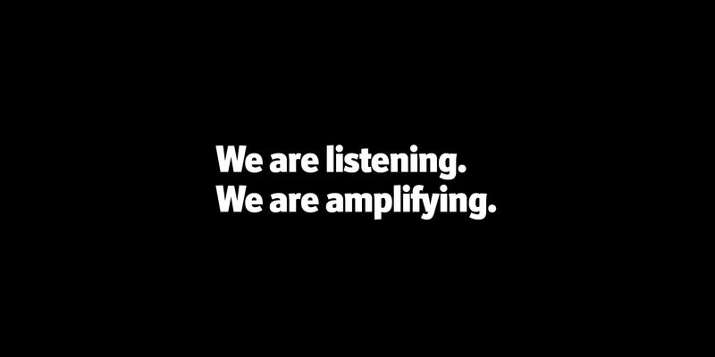 "white text on a black background ""We are listening. We are amplifying."""