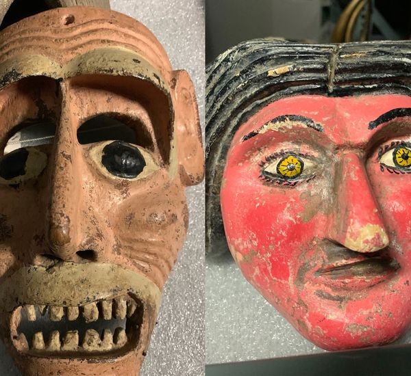 Two masks. On the left a brown mask with bared teeth and black eyes. On the right, a mask with a red face, black hair and yellow eyes.