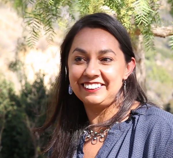 Photo of artist Mercedes Dorame, a woman with long brown hair smiling at someone standing to left of cameral.   She is outside, with a hillside of foliage behind her. She wears a blue shirt and a silver necklace.