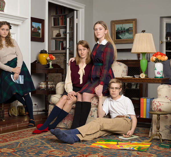 A family portrait of four preteens, arranged in a living room