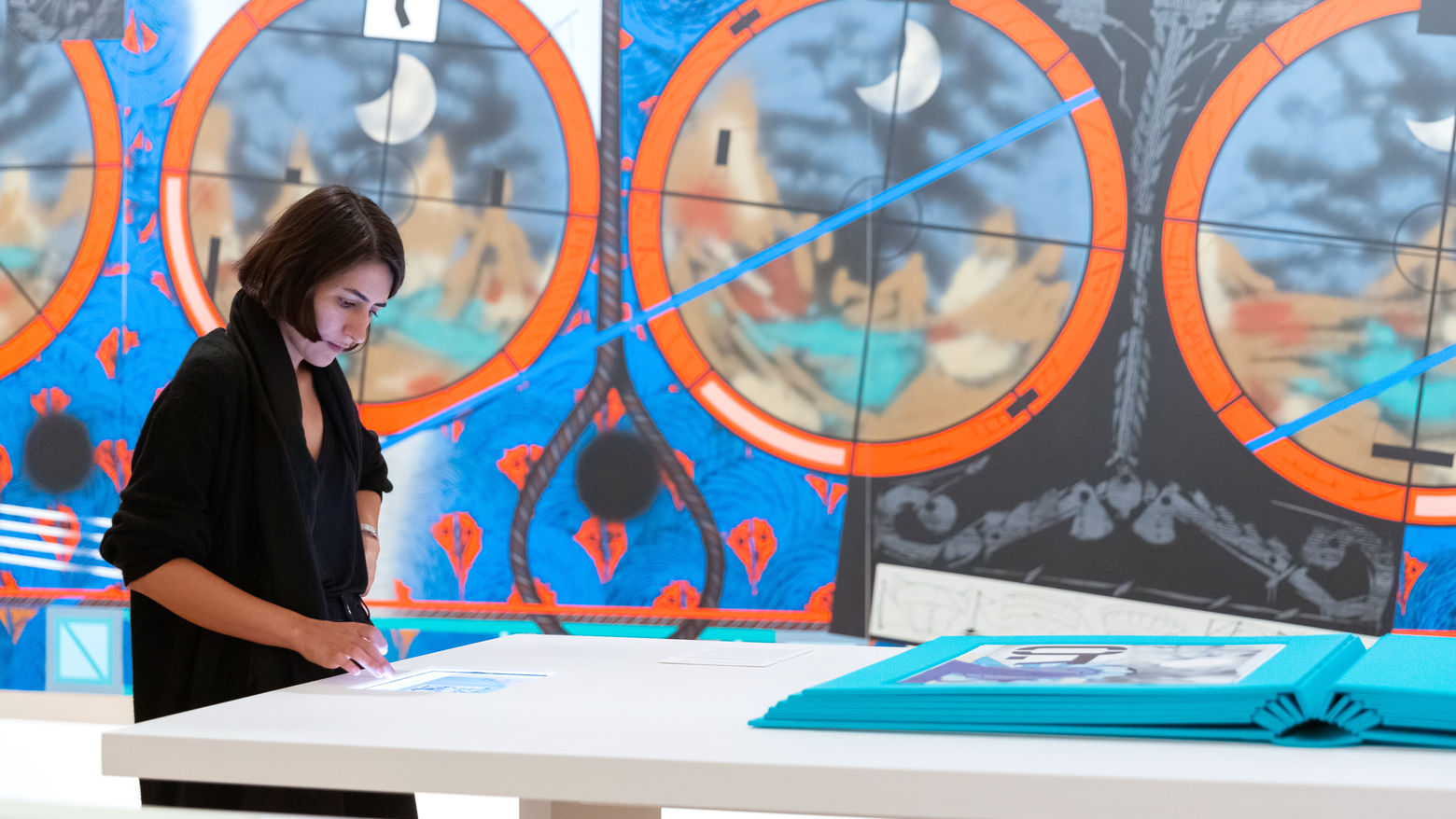 Visitor in a gallery stands, looking down at a device embedded in a table. A very large teal book is also on the table. In the background is a wall-sized painting with geometric designs, red and blue background with black lines.circles,