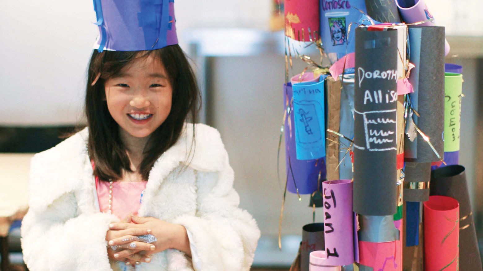 A young girl stands, smiling, wearing a hat made of blue construction paper, a white coat, and silver glitter on her fingers. To the right of her is a structure made of rolls of colored construction paper with words and tinsel.