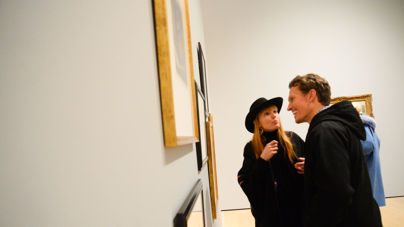 Two people look at paintings on a wall