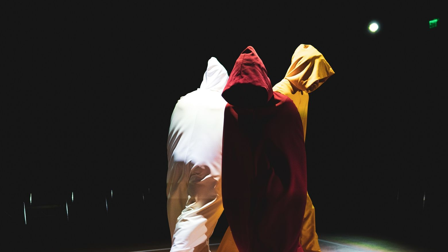 Three figures in hoods walk around a stage