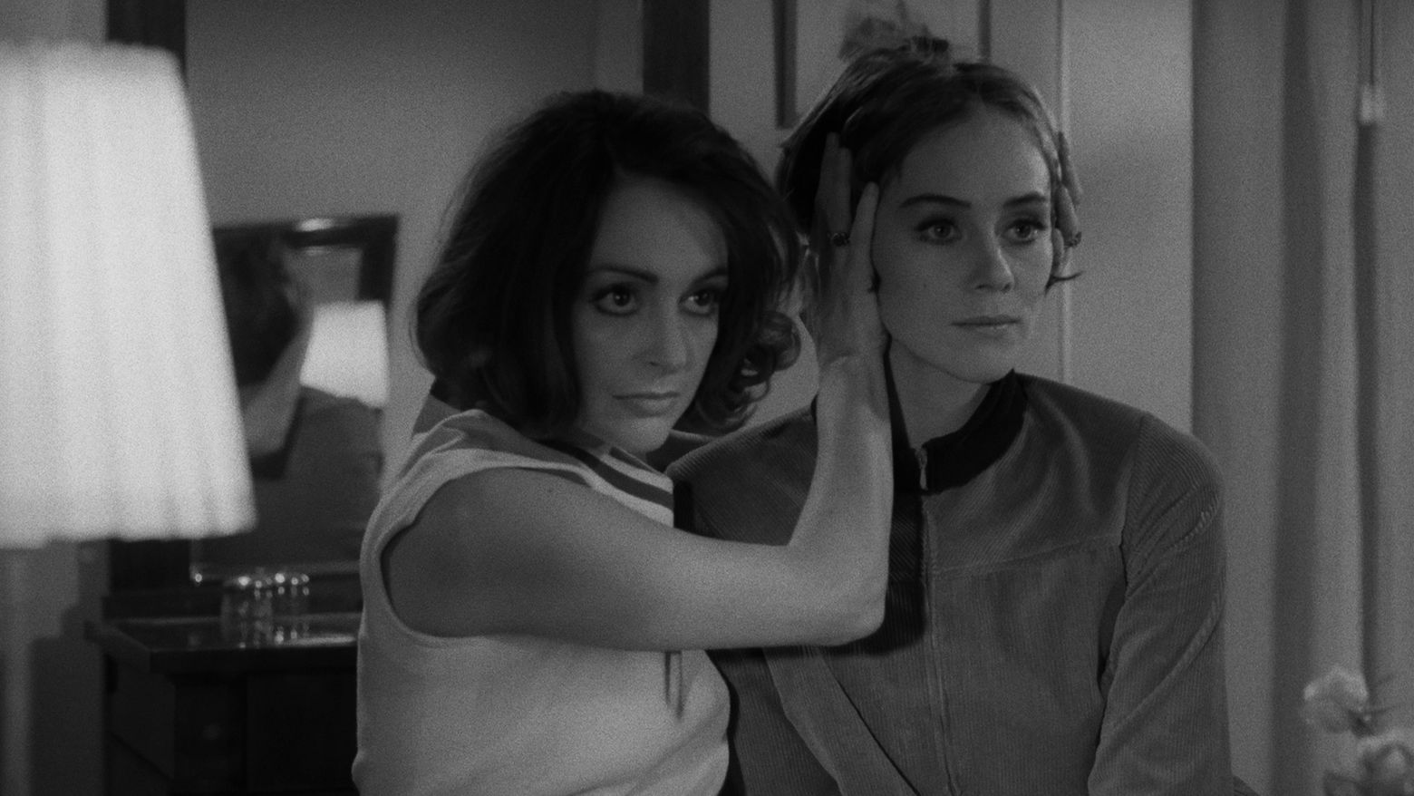 Still from the film Duet for Cannibals (1969) showing a woman holding another woman's head as they both look forward