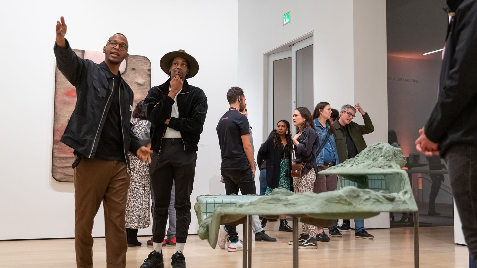 Two young man stand in a gallery next to a sculpture among a crowd