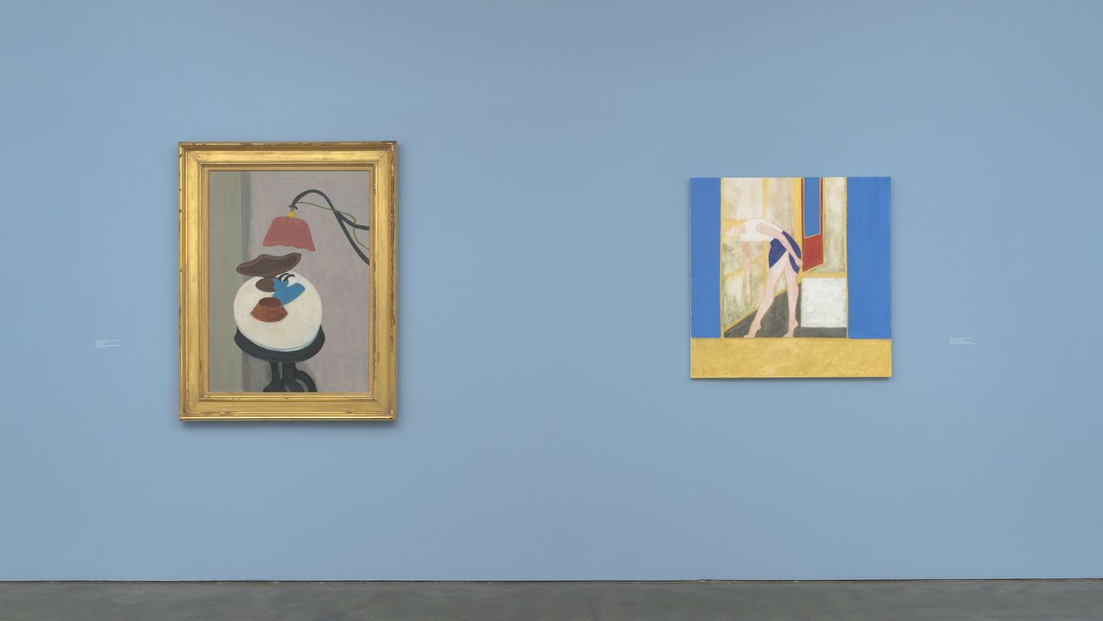 Two paintings hang on a blue gallery wall