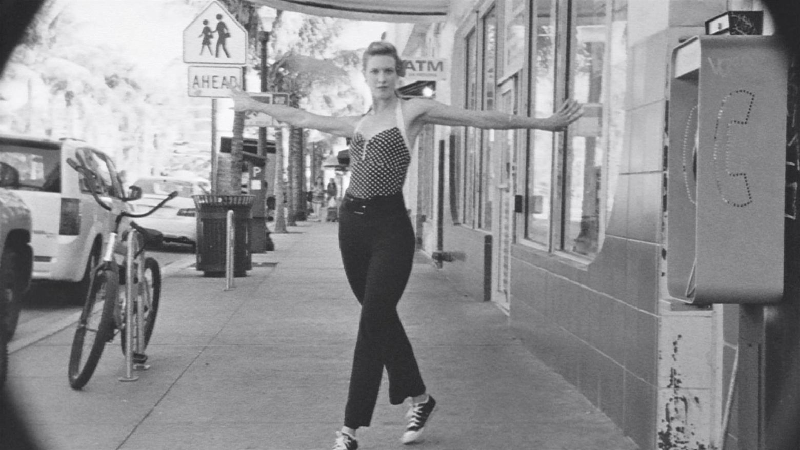 A black-and-white shot of a woman dancing on a sidewalk