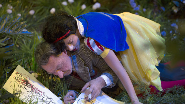 A figure dressed as Snow White lies on top of a man drawing in the grass
