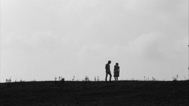 Still from the film Spring Night, Summer Night (1967) showing two people standing on a hill, in shadow