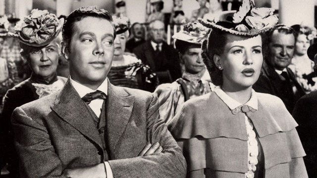 Still from the film The Shocking Miss Pilgrim (1947) showing a man looking askance at a women seated next to him