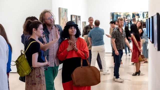 Four people stand in a gallery looking at works of art and talking together.