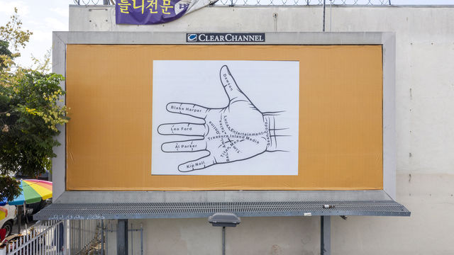 Photo of a billboard against a white building, with a square image of a palmistry diagram in black and white  pasted on top of a gold backgrounf.