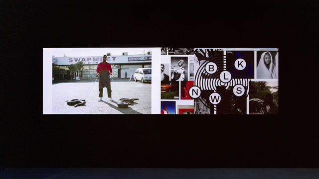 A photograph of two videos projected side-by-side against a black wall that takes up two-thirds of the image. The carpet in the lower third of the photograph is blue.