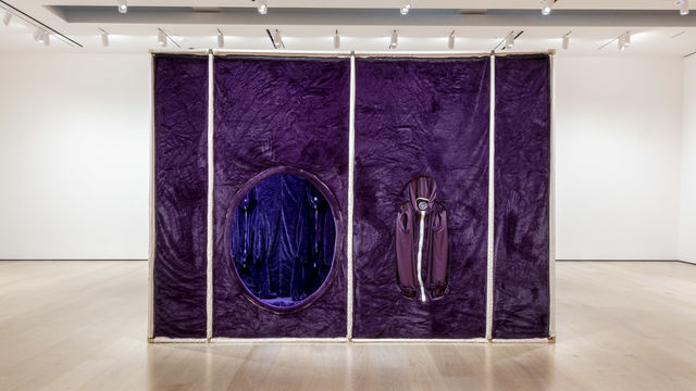 A large gallery with white walls. In the center of the room a large square structure of white poles and purple fabric covering the surface. On the  side of the structure there is a large hole, which provides a view of the inside.