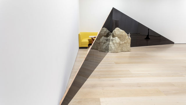 A view of the corner of a gallery. Two dark triangular structures extend across the corner, meeting in the middle at the tall ends. A large rock sits on the floor in front of the triangles, where they meet. Behind the triangles, between them and the wall, a yellow corner booth and a table are visible.