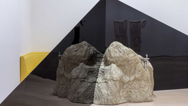 A view of the corner of a gallery. Two dark triangular structures extend across the corner, meeting in the middle at the tall ends. A large rock sits on the floor in front of the triangles, where they meet. A drinking fountain spout extends from the  top of the rock. Behind the triangles, between them and the wall, the edge of a yellow piece of furniture is visible.