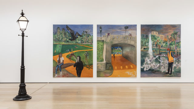 A gallery with a black streetlamp to the left of a triptych of paintings displaying MacArthur Park in Los Angeles
