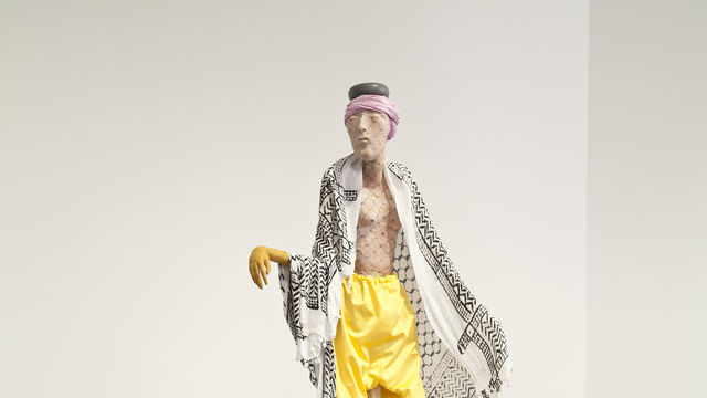 A sculpture of a man dressed in yellow pants stands on a black plinth