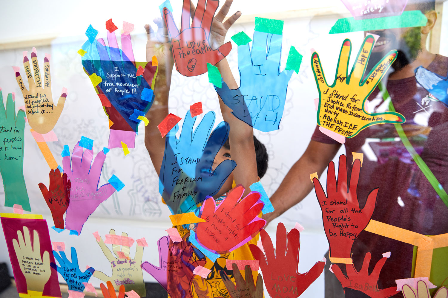 A child presses his hands to a glass covered in paper hand cut-outs