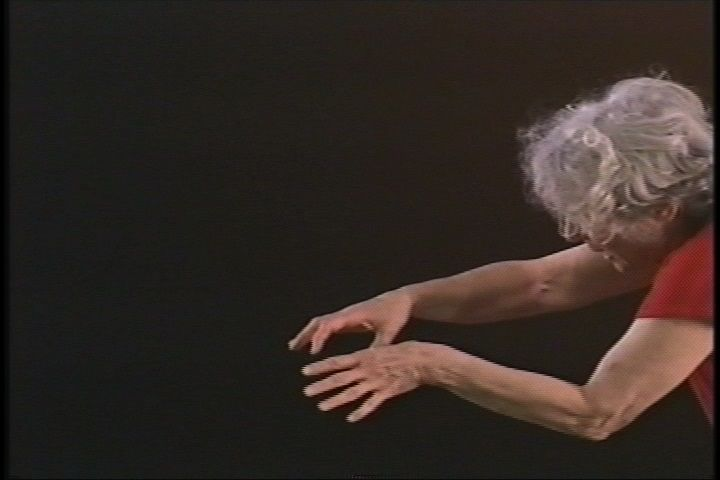 A woman leans into frame with her arms outstretched