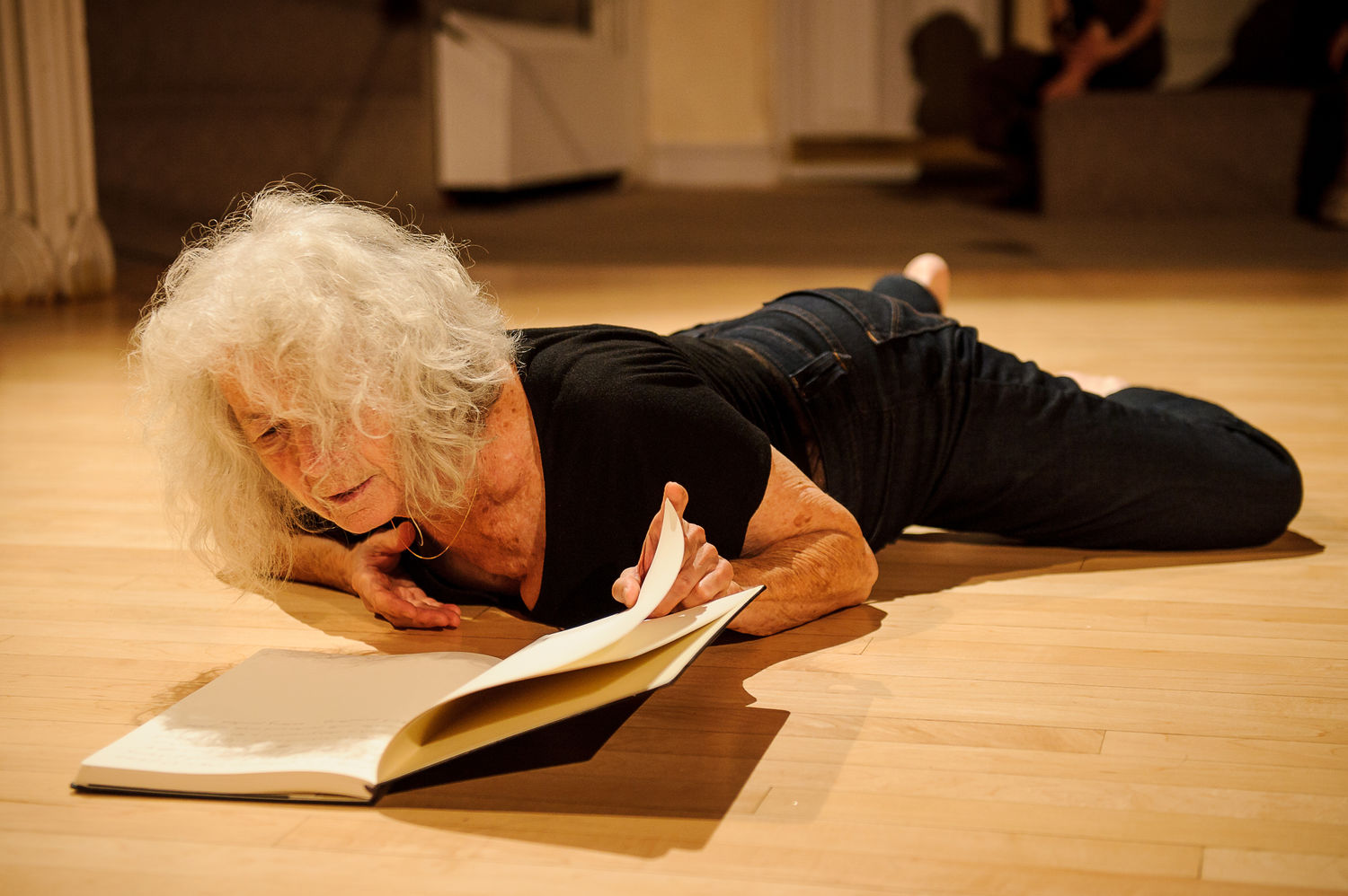 A woman lies on the ground, looking into an open book