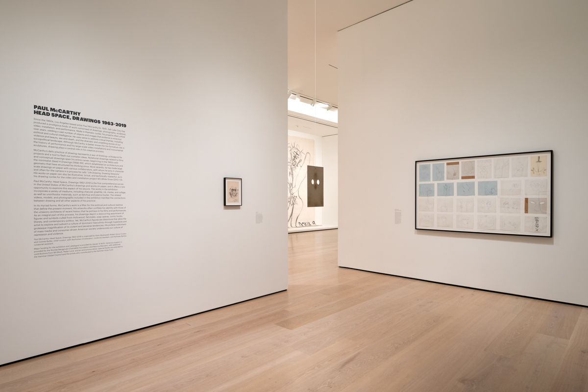 A view of perpendicular gallery walls, with a space between looking into the next room