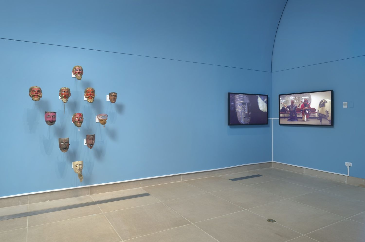 A triangle pattern of masks displayed against a blue wall, next to two monitors in the corner