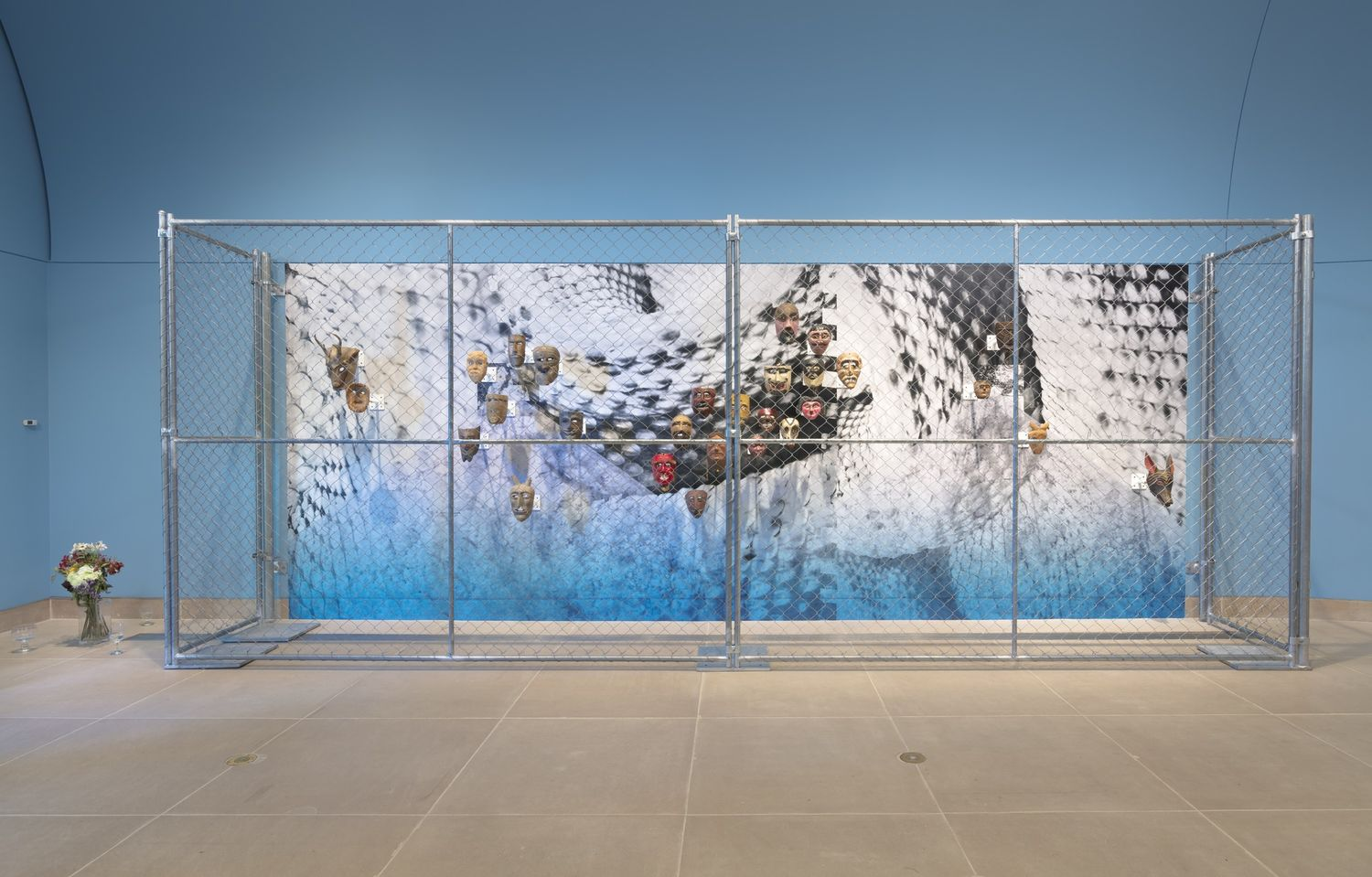 A chainlink fence around a display of masks, set against a snakeskin pattern