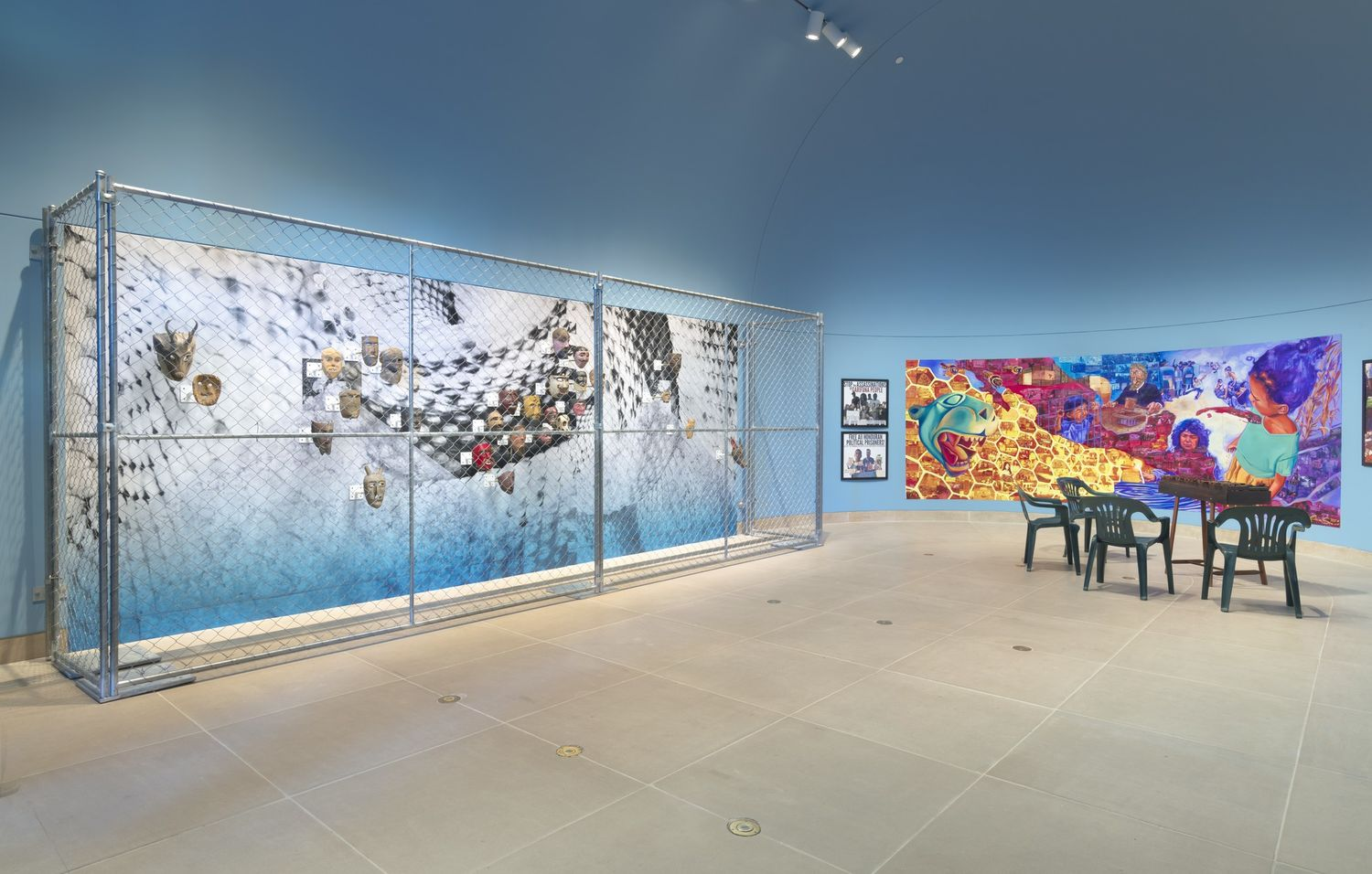 A chainlink fence around a display of masks, with a colorful mural hung on the wall next to them and green chairs on the gallery floor