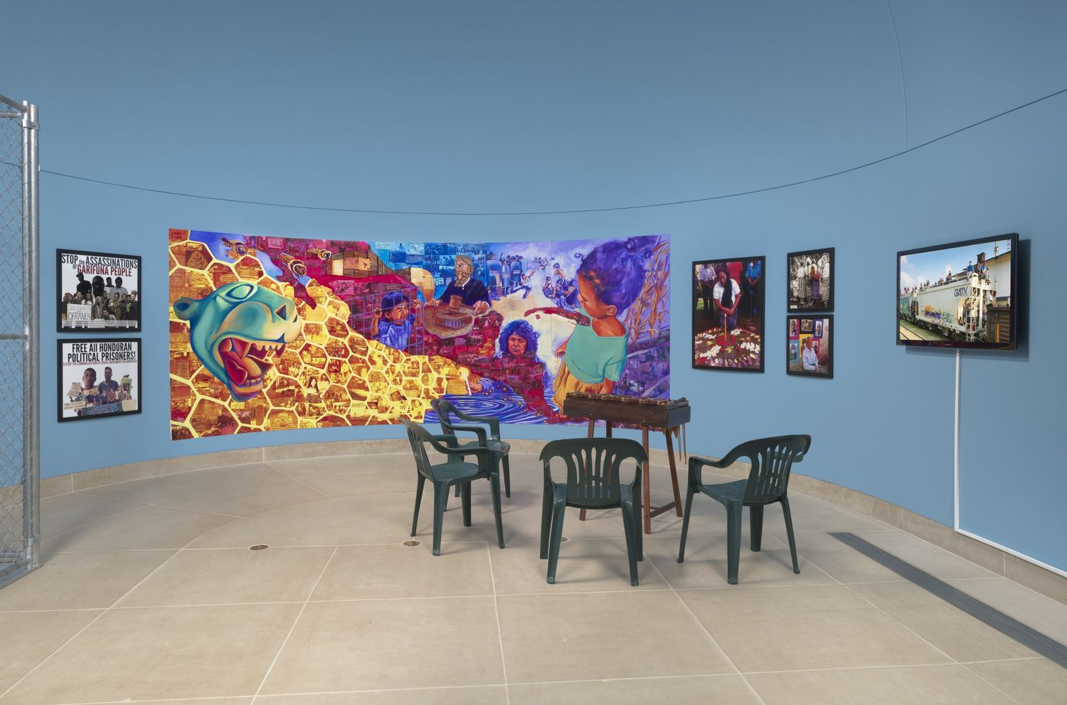 A colorful mural against a pale blue wall with displays on either side, and green chairs on the gallery floor