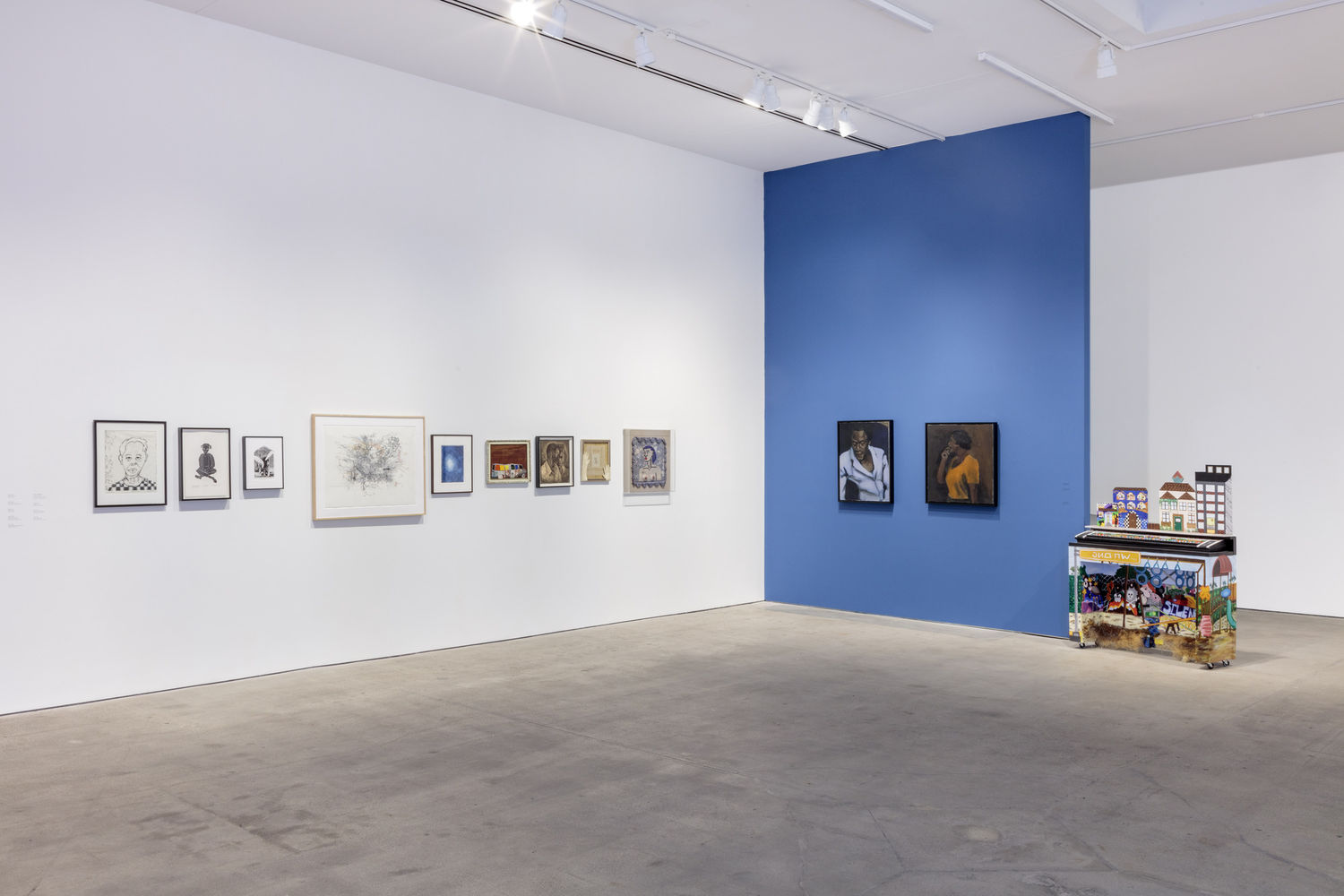 A gallery with a white and a blue wall with several artworks hanging