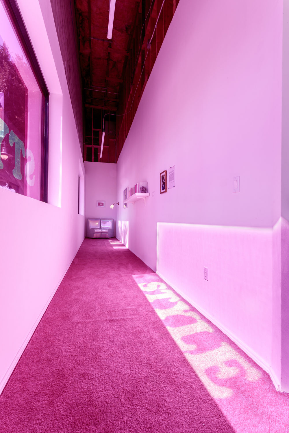 A hallway illuminated with pink light