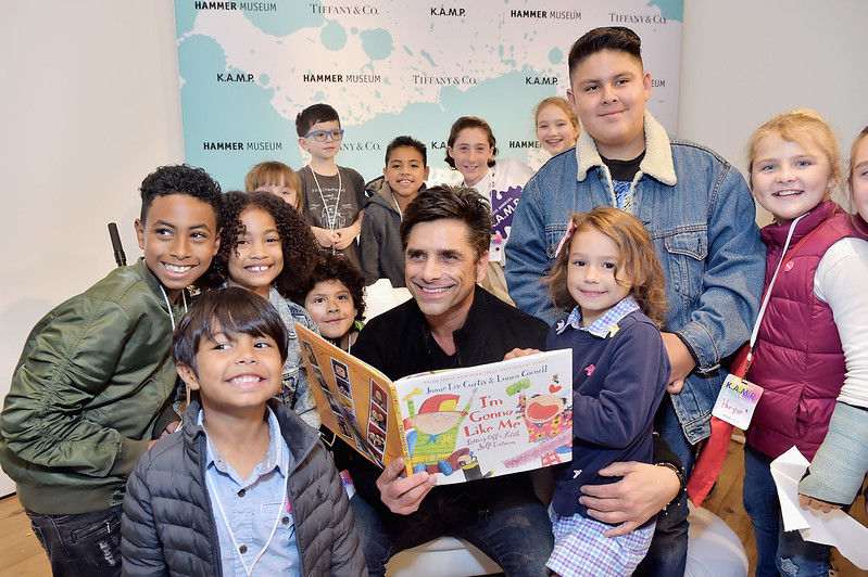 A group of children sit around John Stamos as he reads a book