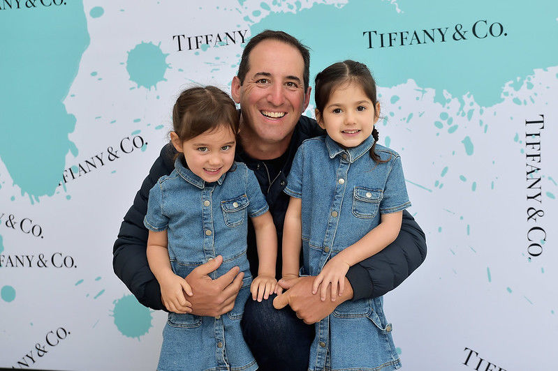 Two young girls in denim jumpers stand with their father before a step-and-repeat