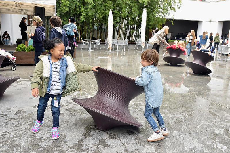 Two children play with a top-like chair