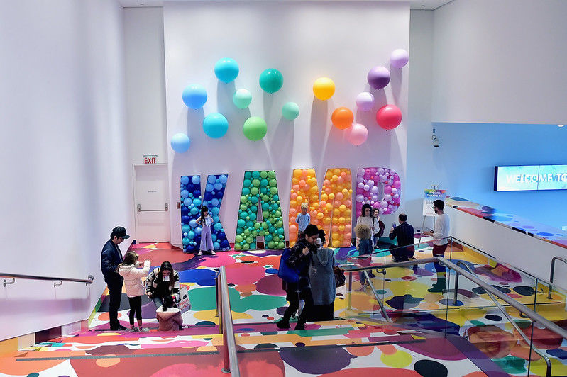 "Colorful balloons spell out ""KAMP"" at the bottom of a colorful staircase"