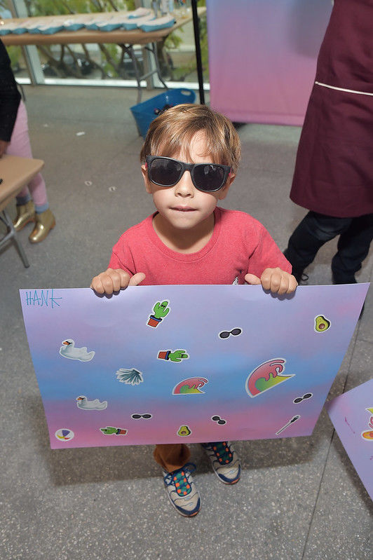 A young boy in sunglasses holds up an artwork
