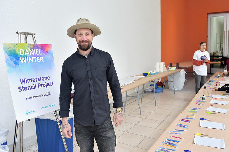 A man in a hat stands before a table of artmaking supplies