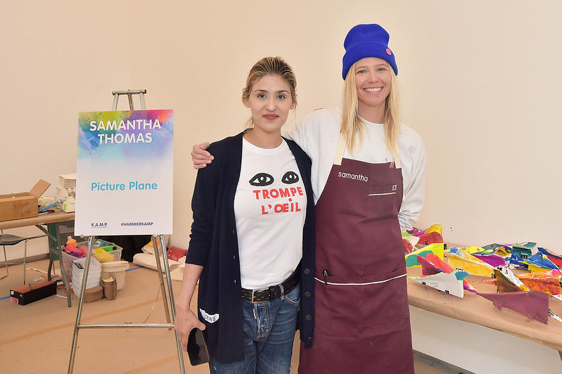 Two women stand before a table of artmaking supplies
