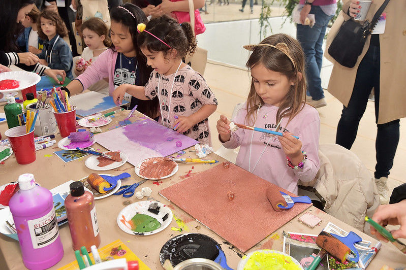 Children face a table of artmaking supplies, playing with brushes and paint