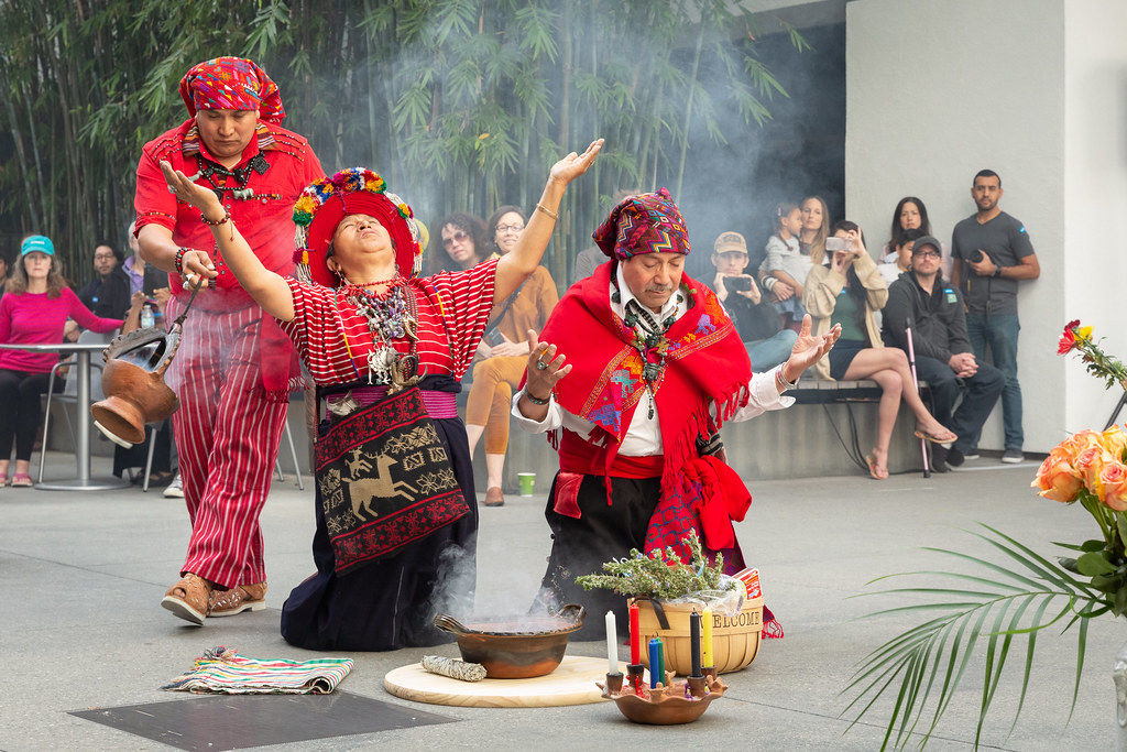 Two dancers kneel while one passes behind them with incense