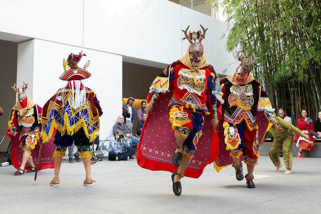 Dancers in deer masks move around a courtyard