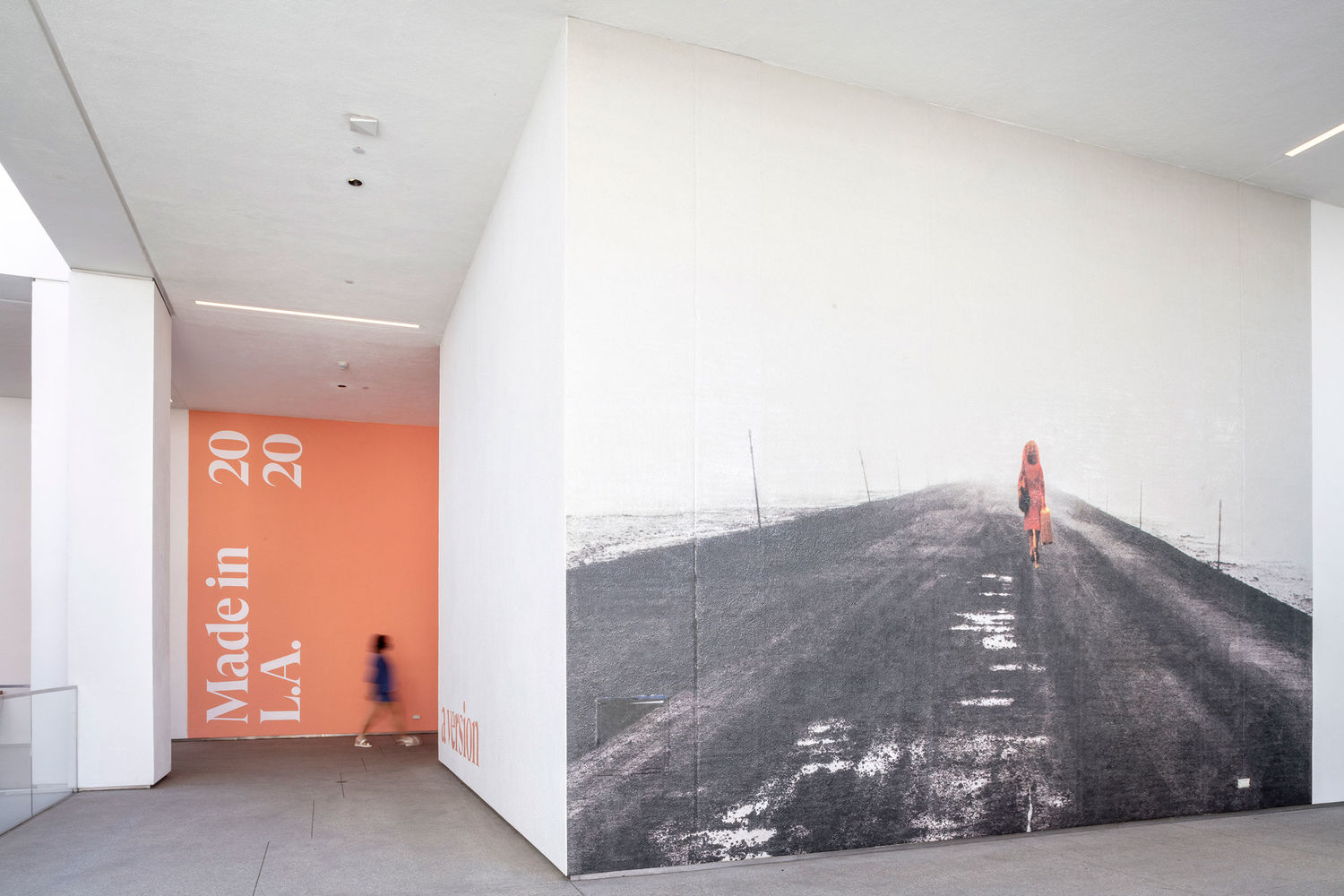 A hallway at the Hammer Museum, with a black-and-white photograph covering a whole wall, and a pink wall with Made in L.A. 2020 on it in the background