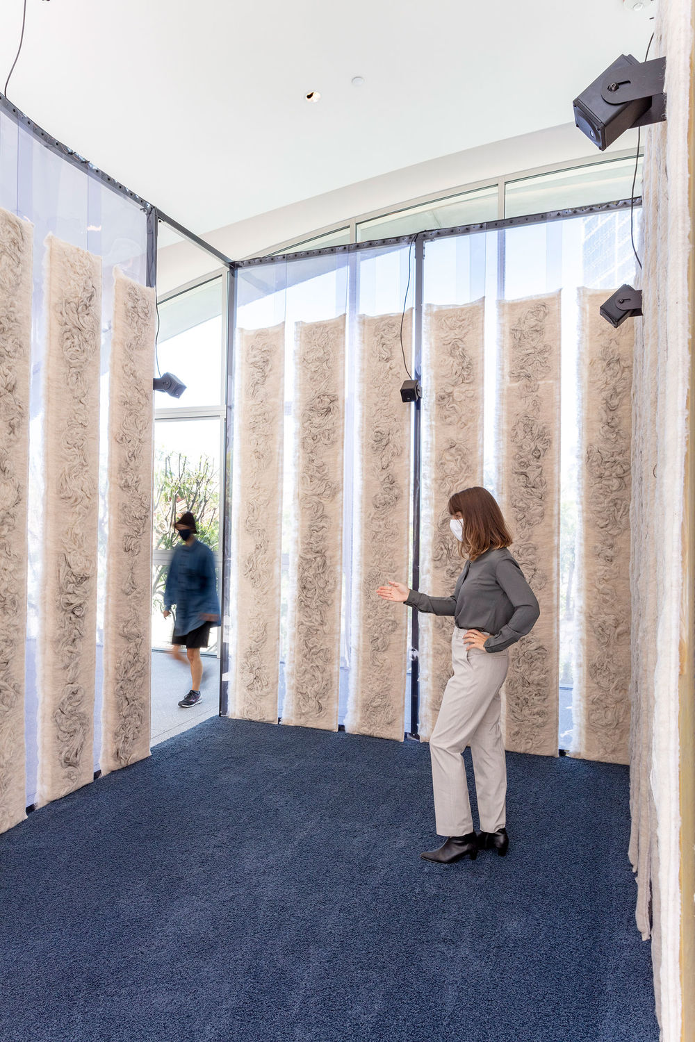 Inside a structure with plastic walls covered in strips of tan fiber, with two women passing through