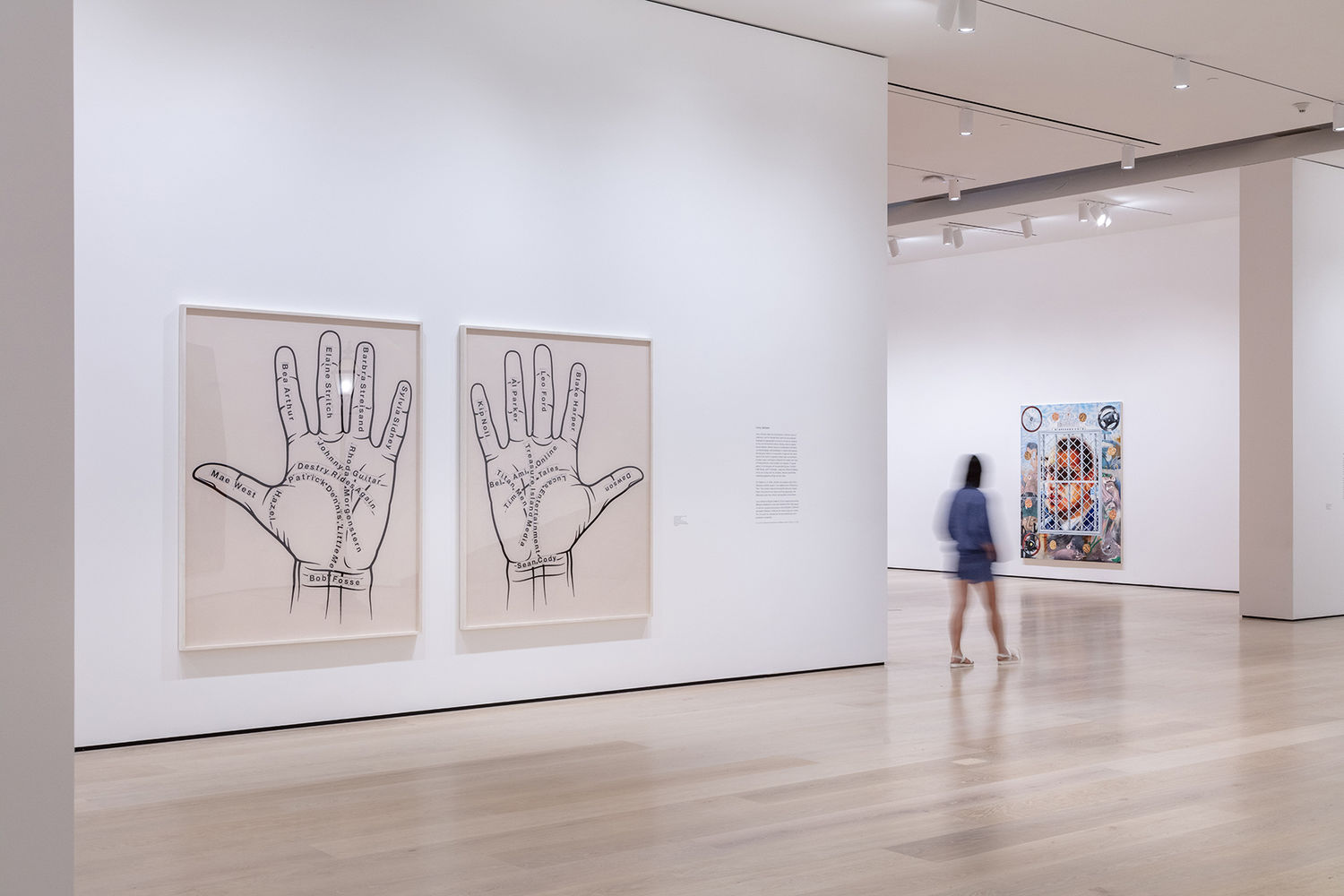 An image inside a white-walled gallery. To the left of the image are two photographs, with a left and right palm in each photo. There are various names written on the palms. In the background is one painting rendered in an airbrush, lowrider car style.
