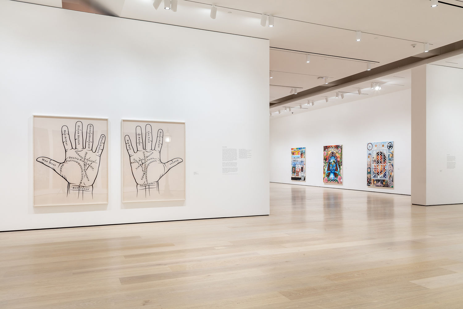 An image inside a white-walled gallery. To the left of the image are two photographs, with a left and right palm in each photo. There are various names written on the palms. In the background are three paintings rendered in an airbrush, lowrider car style.