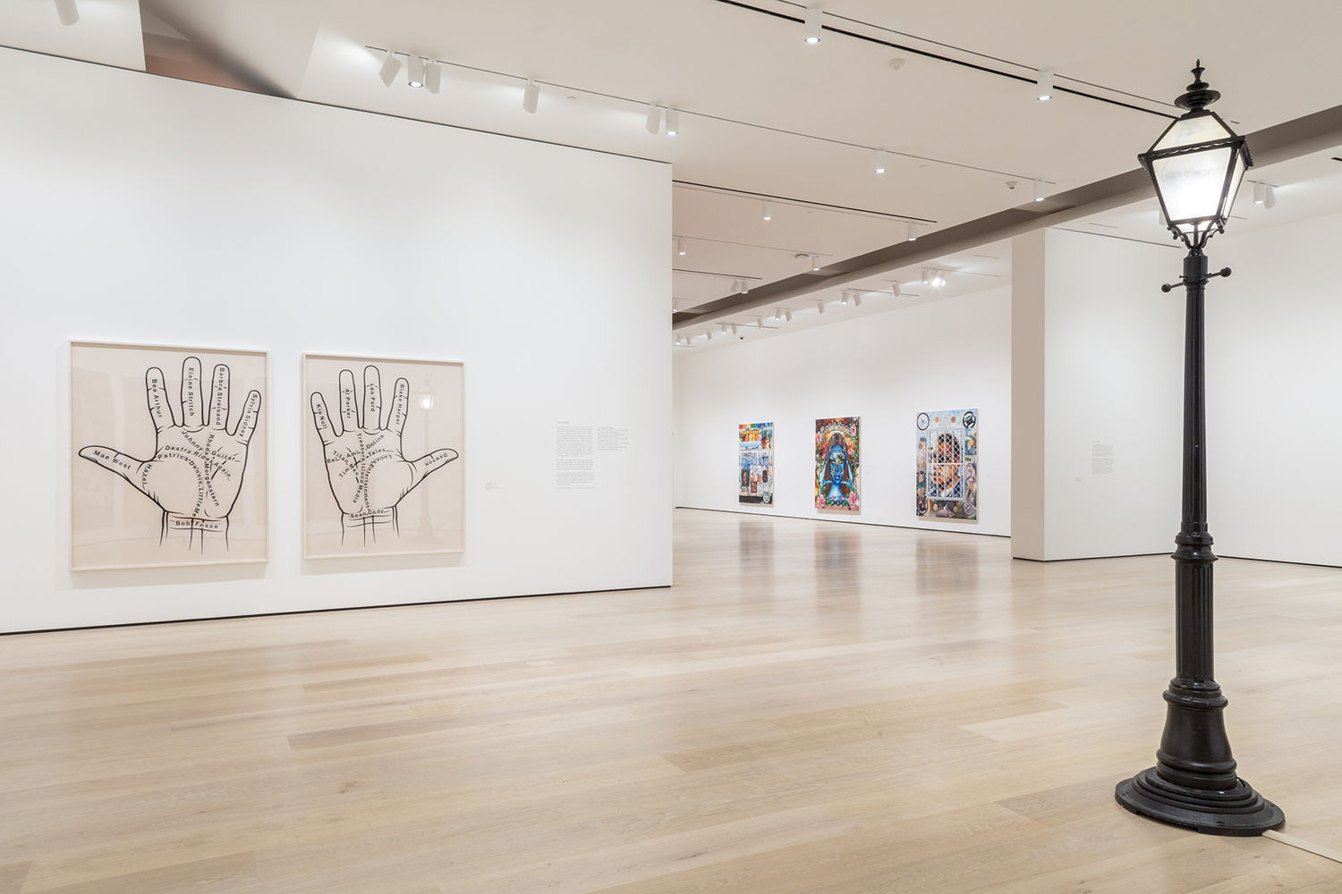 An image inside a white-walled gallery. In the foreground to the right is a black streetlamp. To the left in the middle of the image are two photographs, with a left and right palm in each photo. There are various names written on the palms. In the background are three paintings rendered in an airbrush, lowrider car style.