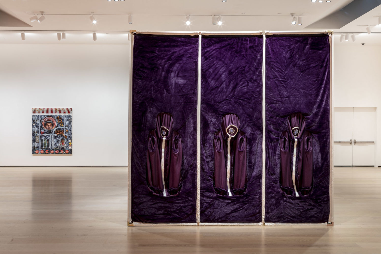 A large gallery with white walls with an artwork on the far wall and in the center of the room a large square structure of white poles and what purple fabric covering the surface. Three panels each have a white circle at head height, with a white stripe down to the floor.