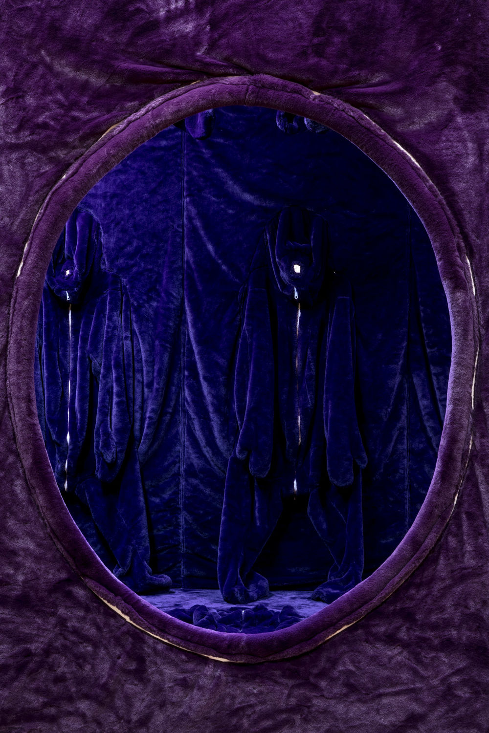 A vertical image shows a circular opening in a wall, looking into a chamber. The wall and chamber are covered in a purple velvet material.